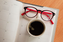 Tasse Kaffee und Gläser auf Notizbuch mit Kalenderplaner Stockfotografie