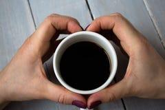 Tasse Kaffee und Hände in der Herzform Stockfotografie