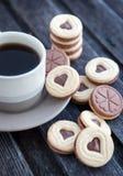 Tasse Kaffee und Herz geformte herausgeschnittene Plätzchen Stockfotografie