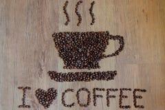 Tasse Kaffee und ich lieben den Kaffee, der auf hölzernen Hintergrund unter Verwendung der Kaffeebohnen gezeichnet wird stockfotos