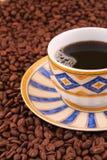 Tasse Kaffee und Kaffeebohnen Stockfotos