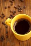 Tasse Kaffee und Kaffeebohnen auf altem Holztisch Lizenzfreies Stockfoto