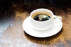 Tasse Kaffee und Kaffeebohnen auf hölzernem Stockfotos