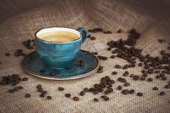 Tasse Kaffee und Kaffeebohnen auf Leinwandhintergrund getont Lizenzfreie Stockbilder