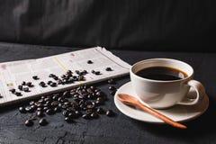 Tasse Kaffee und Kaffeebohnen auf Zeitungspapier auf schwarzem backg stockfoto