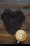 Tasse Kaffee und Kaffeebohnen geformt wie ein Herz Stockfoto