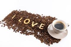 Tasse Kaffee und Kaffeebohnen mit Plätzchen in Form des Liebeswortes Stockbilder