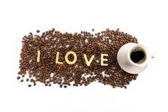 Tasse Kaffee und Kaffeebohnen mit Plätzchen in Form des Liebeswortes Stockbild