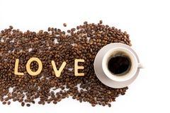 Tasse Kaffee und Kaffeebohnen mit Plätzchen in Form des Liebeswortes Lizenzfreies Stockfoto