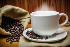 Tasse Kaffee und Kaffeebohnen mit Rauche auf altem hölzernem Stockbild