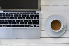 Tasse Kaffee und Laptop auf Holztisch Lizenzfreie Stockfotografie