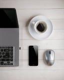 Tasse Kaffee und Laptop, Computermaus, Telefon auf einer Tabelle Stockbild