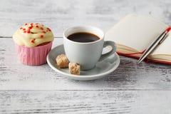 Tasse Kaffee und Muffin auf Bürotisch am Anfang des Arbeitens lizenzfreie stockbilder