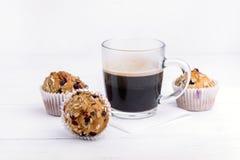 Tasse Kaffee und Muffins mit den Moosbeeren geschmackvoll und schönem Weiß-Hintergrund der kleinen Kuchen Lizenzfreies Stockbild