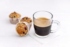 Tasse Kaffee und Muffins mit den Moosbeeren geschmackvoll und schönem Weiß-Hintergrund der kleinen Kuchen Stockfotos