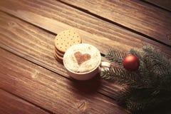 Tasse Kaffee und Niederlassung mit Weihnachtsblasen Stockbilder