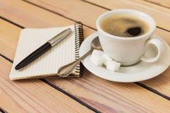 Tasse Kaffee und Notizblock mit Stift auf hölzernem Hintergrund Lizenzfreie Stockfotografie
