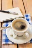 Tasse Kaffee und Notizblock mit Stift auf hölzernem Hintergrund Stockbild