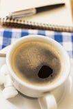 Tasse Kaffee und Notizblock mit Stift auf hölzernem Hintergrund Lizenzfreies Stockbild