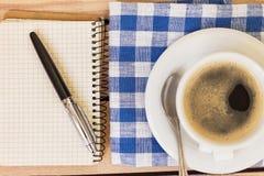Tasse Kaffee und Notizblock mit Stift auf hölzernem Hintergrund Lizenzfreie Stockfotos
