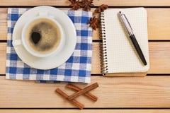Tasse Kaffee und Notizblock mit Stift auf hölzernem Hintergrund Lizenzfreies Stockfoto
