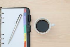 Tasse Kaffee und Notizbuch Stockbild