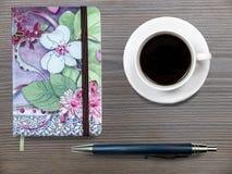 Tasse Kaffee und Notizbuch Lizenzfreie Stockfotos