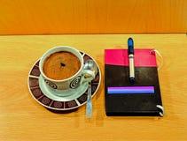 Tasse Kaffee und Notizbuch Stockfotos