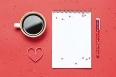 Tasse Kaffee und Notizbuch auf rotem Hintergrund Minimalistic-Art Draufsicht, flache Lage Lizenzfreie Stockfotografie