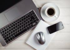 Tasse Kaffee und Notizbuch, Laptop, Computermaus, Telefon auf einem t Lizenzfreie Stockfotos
