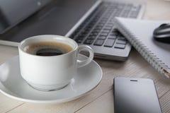 Tasse Kaffee und Notizbuch, Laptop, Computermaus, Telefon auf einem t Stockbild