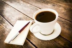 Tasse Kaffee und Notizbuch nahe bei ihm. Stockfotografie