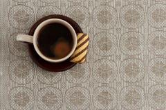 Tasse Kaffee und Plätzchen auf Platte gegen einfarbige Tischdecke mit Kopienraum Lizenzfreies Stockfoto
