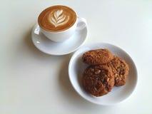 Tasse Kaffee und Plätzchen auf Weiß Stockfotografie