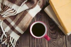 Tasse Kaffee und Plaid und alte Bücher auf dem Tisch Stockfoto