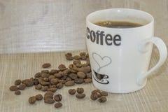 Tasse Kaffee- und Röstkaffeebohnen auf einem Holzfuß Stockfoto
