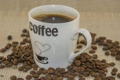 Tasse Kaffee- und Röstkaffeebohnen auf einem Holzfuß Lizenzfreie Stockfotos