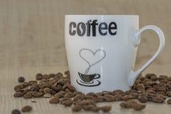 Tasse Kaffee- und Röstkaffeebohnen auf einem Holzfuß Stockbild