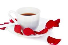 Tasse Kaffee und rosafarbene Blumenblätter. Lizenzfreie Stockfotografie