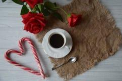 Tasse Kaffee und Rosen mit Dekorationen für Valentinsgrußtag Stockfotos