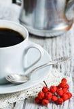 Tasse Kaffee und rote Ebereschebeeren Stockbilder