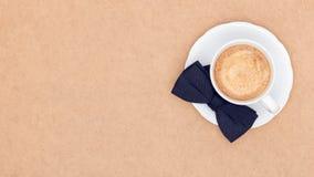 Tasse Kaffee und schwarze Fliege auf brauner Hintergrundebenenlage Vatertagsstillleben Lizenzfreie Stockbilder
