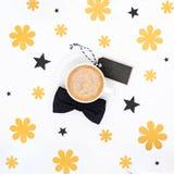 Tasse Kaffee und schwarze Fliege auf weißer Hintergrundebenenlage Blumenvatertags-Stilllebeneinrichtung Stockbild