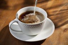 Tasse Kaffee und strömender Rahmtopf stockfoto