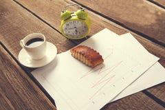 Tasse Kaffee und Uhr auf Dokumentenpapier lizenzfreies stockfoto
