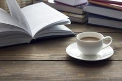 Tasse Kaffee und viele Bücher Stockbild
