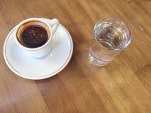 Tasse Kaffee und Wasser auf Tabelle Stockbilder