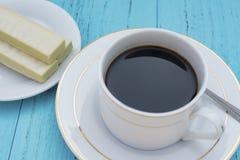 Tasse Kaffee und weiße Schokoladenoblate auf blauem ackground Lizenzfreies Stockfoto