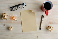 Tasse Kaffee und zerknittertes Papier mit leerem Papier auf Schreibtisch, Stockfotografie