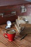 Tasse Kaffee, Weinlesekoffer, Uhren, Gläser und alte Bücher Stockfotos